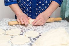 Sheeting the dough with a rolling pin in the kitchen.  Royalty Free Stock Photos