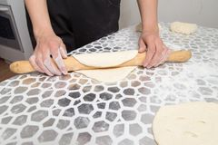 Sheeting the dough with a rolling pin in the kitchen.  Stock Photos