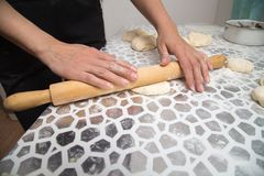 Sheeting the dough with a rolling pin in the kitchen.  Stock Photo