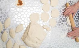 Sheeting the dough with a rolling pin in the kitchen.  Stock Photography