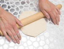 Sheeting the dough with a rolling pin in the kitchen.  Royalty Free Stock Images