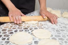 Sheeting the dough with a rolling pin in the kitchen.  Royalty Free Stock Photography