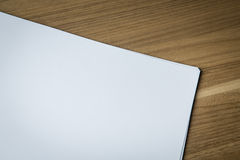 Sheets of blank paper on wooden desk Royalty Free Stock Photo