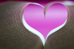 Sheets of a book heart shaped with pink color background Royalty Free Stock Photos