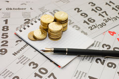 Sheets of a calendar with coins and a notebook Royalty Free Stock Photography