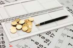 Sheets of a calendar with coins and a notebook Stock Photo