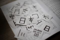 Sheets with a lot of chinese and japanese language characters kanji with main word Japan translation - man, like, eye and other. Kanji written on paper on white royalty free stock image