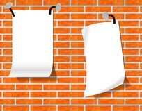 Sheets of paper on a brick wall. Royalty Free Stock Photo