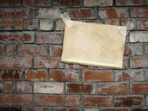 Sheets paper, hanging on a brick wall Royalty Free Stock Photos