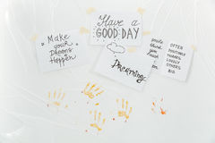 Sheets of paper with motivational phrases and palms prints. Over white background Royalty Free Stock Photo