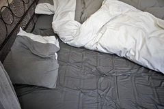 Sheets and pillows of an unmade bed Stock Images