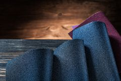 Sheets of sand paper on dark wood background stock images
