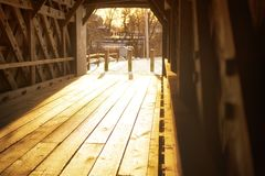 Sheffield Massachusetts covered bridge sunset. Sunlight within the historic sheffield massachusetts covered bridge spanning the Housatonic River on a cold winter royalty free stock image