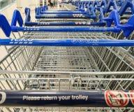 SHEFFIELD, REINO UNIDO - 20 DE MARZO DE 2019: Las carretillas de las compras parquearon en una línea dentro de un supermercado de fotografía de archivo libre de regalías