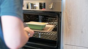Sheffield, Reino Unido - 29 de mayo de 2019: Un varón caucásico blanco pone una comida para una en un horno de la fan de la aspir almacen de video
