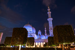 Sheikh Zayed Grand Mosque Centre Abu Dhabi illuminated at night with blue color. The white terraces. Royalty Free Stock Photo