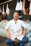 SHEKI AZERBAJDZJAN - 20 Juli 2015: stående av manligt säljarekött som ser kameran Royaltyfri Foto