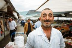 SHEKI AZERBAJDZJAN - 20 Juli 2015: stående av manligt säljarekött som ser kameran Royaltyfri Fotografi