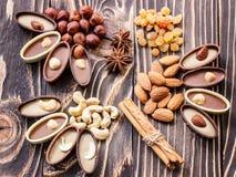 Shekoladnye糖果、坚果和葡萄干在一张木桌上 库存图片