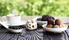 Shekoladnye dei dolci e della tazza di caffè sulla tavola di legno Immagini Stock