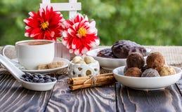 Shekoladnye della tazza di caffè, dei fiori e dei dolci su un tabl di legno Fotografie Stock Libere da Diritti