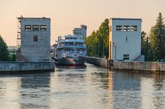 Sheksna River, Russia - 07.19.2018: The passenger cruise ship Two Capitals passes through the gateway of sluice on the Sheksna royalty free stock image