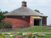Shelburne Museum. The round barn with all it's colorful flowers is at the entrance to the popular and interesting Shelburne Museum. Round barns were once found Royalty Free Stock Photos
