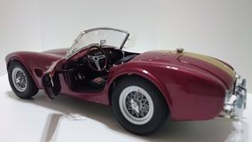 Shelby Cobra cabrio roadster in golden stripes on burgundy paint Stock Photos