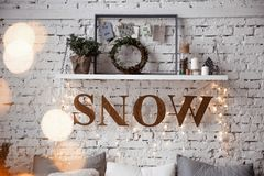 A shelf above the bed on the background of a brick wall loft decorated with retro garland. royalty free stock photography