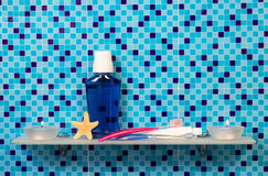Shelf with bath accessories. Bath accessories on shelf and blue background Stock Image