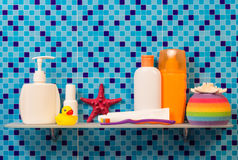 Shelf in bathroom with children's hygiene on abstract blue. Stock Images