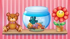A shelf with a bear, an aquarium and a toy flower Stock Photos