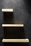 Shelf and black wall on wooden Stock Photos