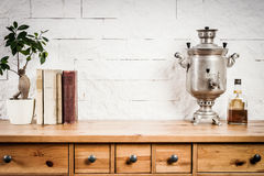 Shelf with a book and a flower and a kettle Royalty Free Stock Photos