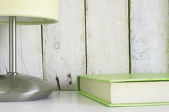 Shelf with a book and a lamp, ready for reading time. Stock Images