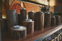 Shelf with candles in wooden candlesticks. Cozy home rustic decor stock photo