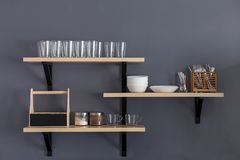 Shelf with clean dishware. Stylish shelf with various dishware hanging on gray wall stock photography
