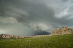 A shelf cloud accompanies this thunderstorm as it approaches a rocky hillside. stock image