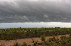 Shelf Cloud Over Beach. The underside of a shelf cloud, a type of arcus cloud, over a beach. This is the leading edge of a severe thunderstorm in progress stock images