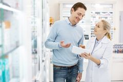 Charming female pharmacist finding medication. On this shelf. Confident female pharmacist using tablet while speaking with man stock photo