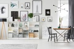 Shelf in dining room. White shelf with decorations set in a dining room interior with posters on the wall royalty free stock photos