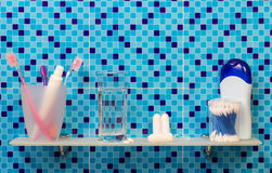 Shelf with feminine hygiene products in bathroom on abstract blue. Royalty Free Stock Images
