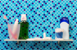 Shelf with feminine hygiene products in bathroom on abstract blue. Royalty Free Stock Image