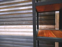 Shelf In Front Of Metal Foldable Corrugated Door. Shelf In Front Of Closed Metal Foldable Corrugated Door Royalty Free Stock Photo