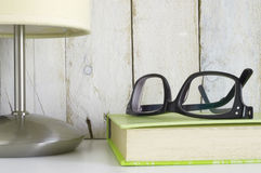 Shelf with glasses on a book and a lamp, ready for reading time. Stock Images