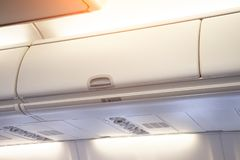 Shelf for hand luggage over the passenger seats in the plane stock images
