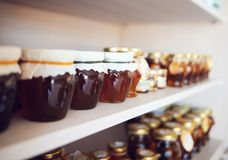Shelf with home-made honey and jam Stock Photography