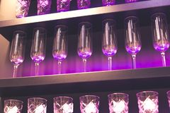 Shelf with a lot of empty wine glasses with pink and violet light. Bar or glassware shop interior. Celebration, event or. Party concept stock photos