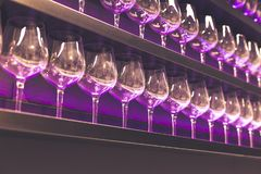 Shelf with a lot of empty wine glasses with pink and violet light. Bar or glassware shop interior. Celebration, event or. Party concept stock image
