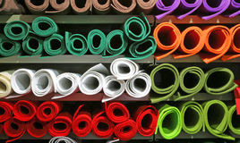 Shelf with Many colored felt rolls for sale in the market stall. In large fabric store Royalty Free Stock Photography